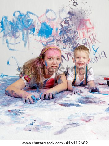 Child himself dirty in the paint and looks into the camera. Child has fun and stain the wall. Children's creativity. Art for baby. Child and mother drawing on wall and floor.  - stock photo