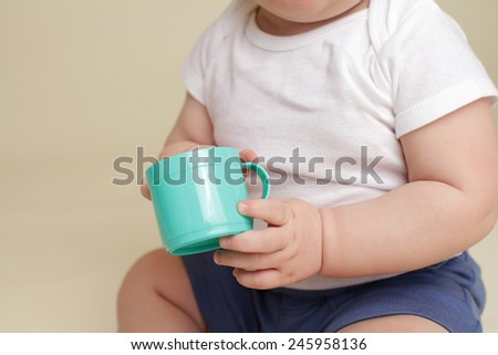 Child holding a cup, eating or drinking, baby nutrition concept - stock photo
