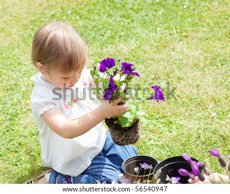 Child holding a flower in her hands - stock photo
