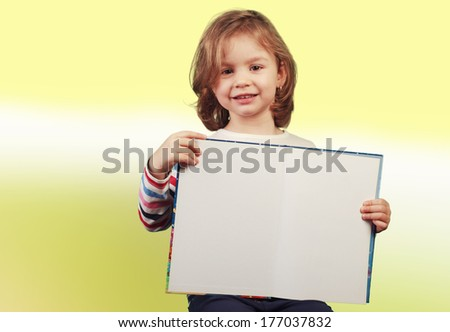 Child holding a open book on yellow-green background - stock photo