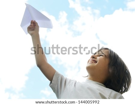 Child holding a paper airplane and dreaming about traveling - stock photo