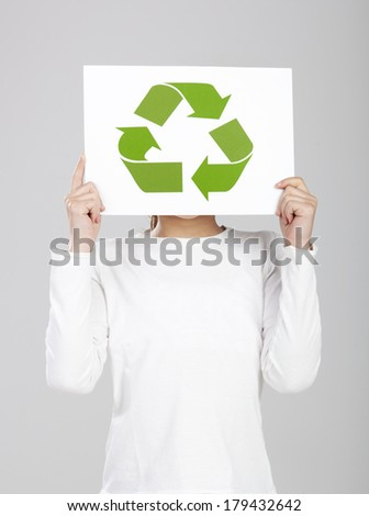 Child holding a paper with the recycle symbol on it, isolated over a white background - stock photo
