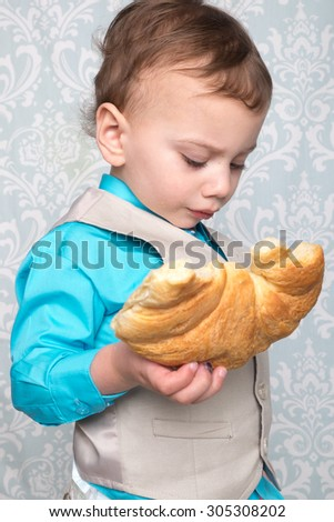 Child holding a partially eaten croissant  - stock photo