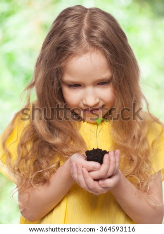 Child holding a seedling. Girl with sprout - stock photo