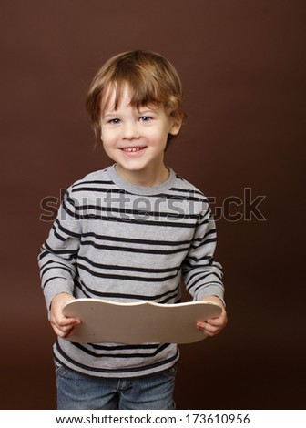 Child holding an empty wood frame, sign - stock photo