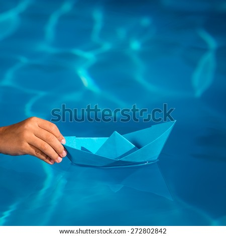 Child holding blue paper sailing boat on water background. Summer vacation and travel concept