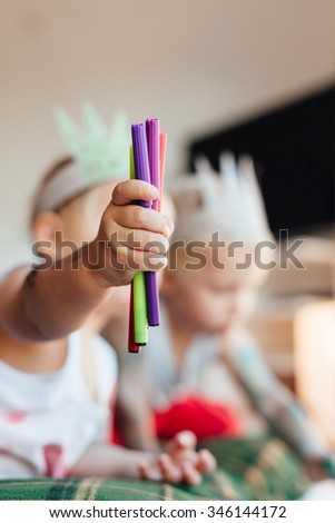 Child holding colorful markers