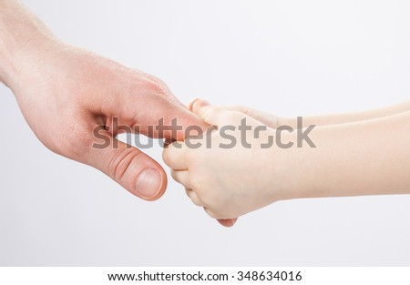 Child holding father's finger, closeup shot of hands - stock photo