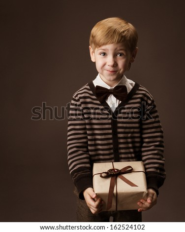 Child holding gift box. Boy portrait with present in vintage style. - stock photo