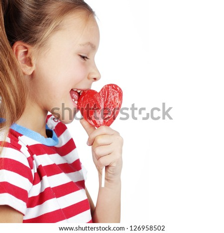 Child holding heart shaped candy isolated studio shot