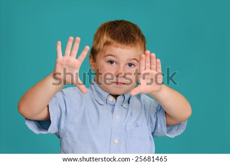 Child holding his hands up in front of him - stock photo