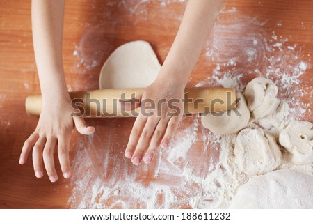 Child holding kneading dough. Kid's hands and fresh dough, flour and rolling-pin on table. Cooking pies at home or  learning at culinary class.