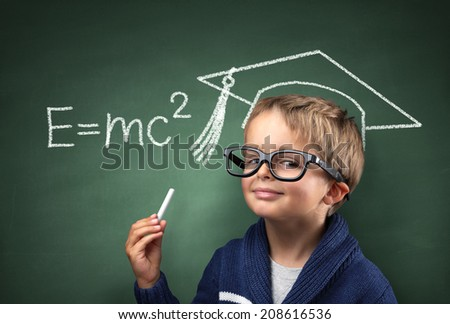 Child holding piece of chalk with E=mc2 and mortar board drawing on blackboard concept for genius student, university education and future aspirations - stock photo