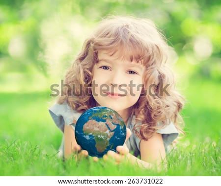 Child holding planet in hands against green spring background. Earth day holiday concept. Elements of this image furnished by NASA - stock photo