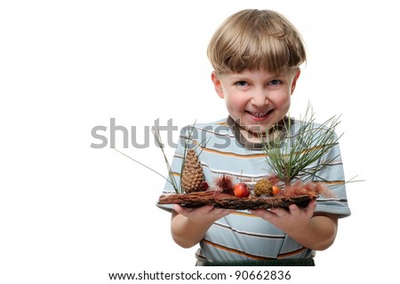 Child holding self made christmas or winter decoration in the hands. Isolated on white background.