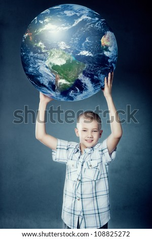Child holding the earth in his hands on gray background. Elements of this image furnished by NASA. - stock photo