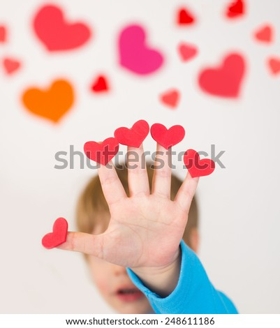 Child, holding up valentine's day hearts on fingers of his hand, love concept - stock photo