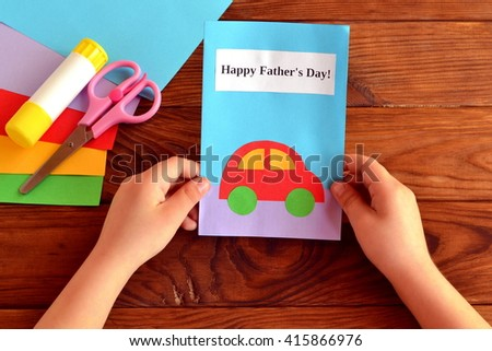 Child holds a card in his hand. Greeting card Happy father's day. Paper sheets, scissors, glue. How to make a greeting card father's day  - stock photo