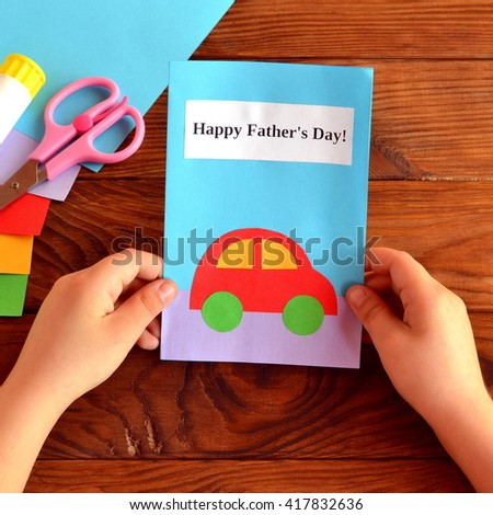 Child holds a card in his hands. Greeting card Happy father's day. Paper sheets, scissors, glue. How to make a greeting card father's day  - stock photo