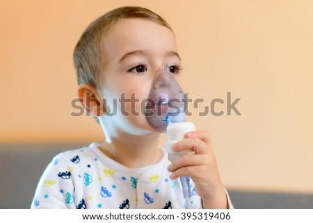 Child holds a mask vapor inhaler - stock photo