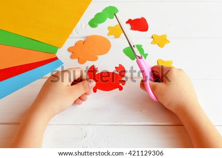 Child holds a scissors and cuts paper crab. Art lesson in kindergarten. Paper sea animals - octopus, fish, starfish, seahorse, crab. Kids crafts  - stock photo