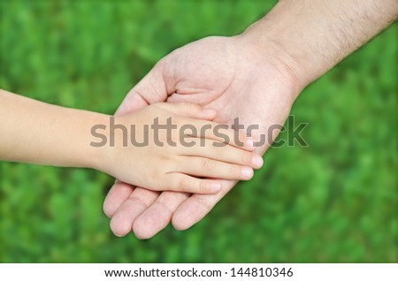 Child holds the hand of the father outdoor - stock photo