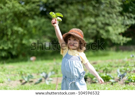 Child holds up radishes