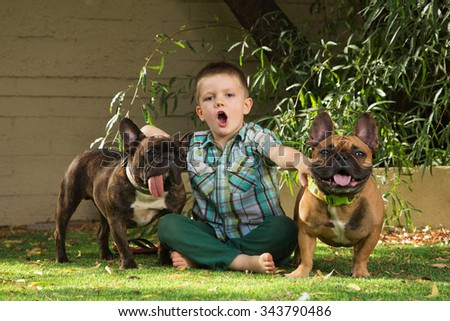 Child howling with pair of bulldogs outdoors - stock photo