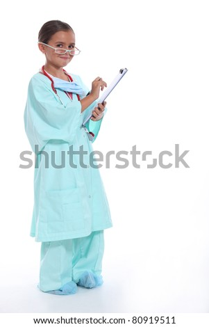 Child in a doctors scrubs with stethoscope and clipboard - stock photo