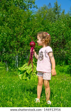 child in a garden with beet in a hand