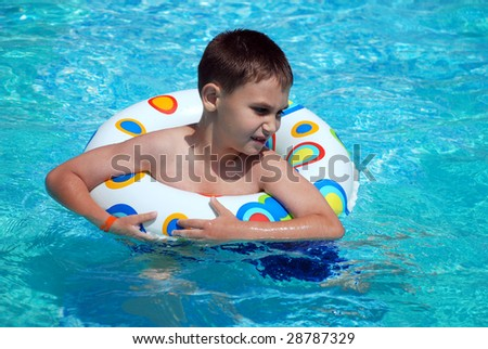 Child in a swimming pool having his first swim lessons