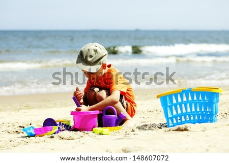Child in action little boy playing toys on beach sea background