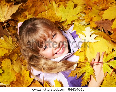 Child in autumn orange leaves. Outdoor.