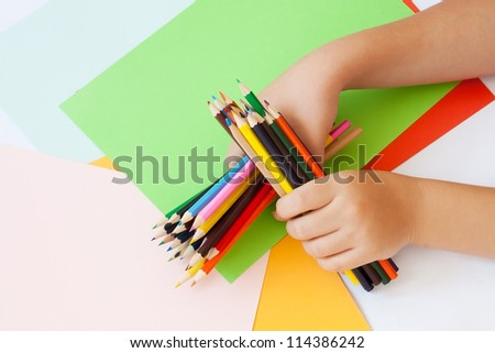 Child in both hands holding colored pencils. Paper in more colors in the background. - stock photo