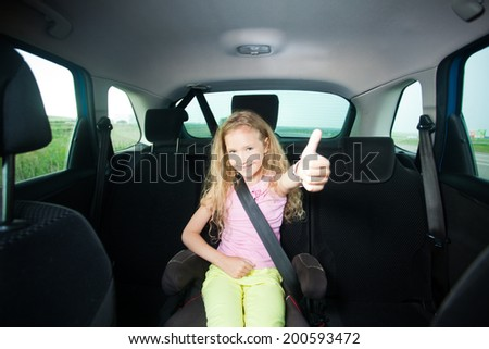 Child in car. Happy girl wearing seatbelts - stock photo