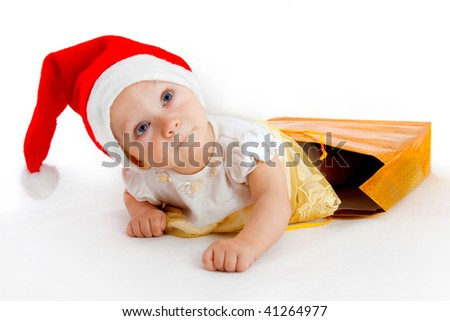 child in christmas hat crawl out from the bag with presents