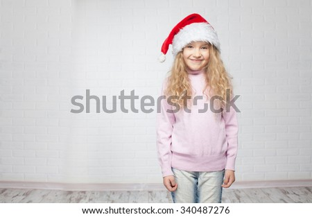 Child in christmas hat on white background. Happy little girl - stock photo