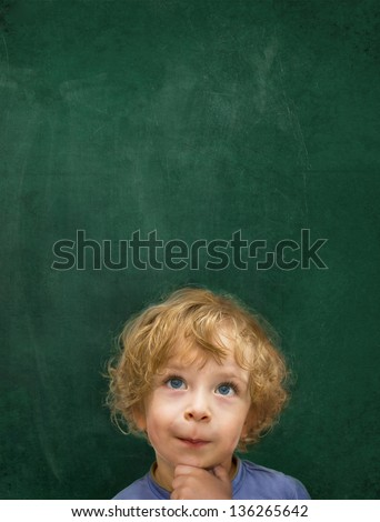 Child in front of a green chalkboard - stock photo