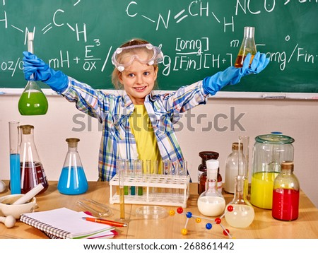 Child in glove holding flask in chemistry class. - stock photo