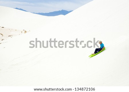 Child in green sled rolls with large sand dunes. White Sands National Monument, New Mexico