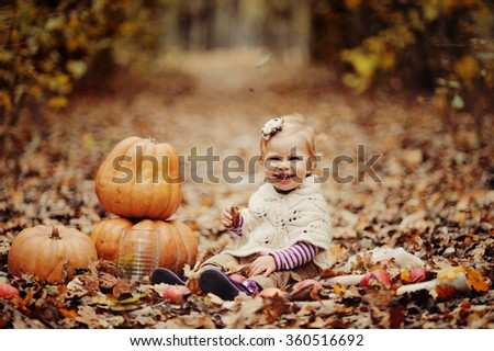 child in in warm white knitted clothes against big pumpkins