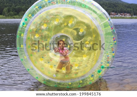 Child in inflatable attraction on the lake.