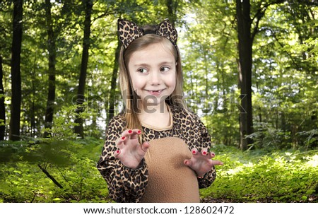 child in leopard costume showing her claws in the wood - stock photo