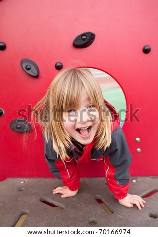 child in playground happy smiling. pretty blond boy with long hair full of joy. Childhood image of play - stock photo