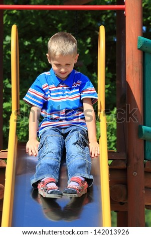 child in playground kid in action boy play on leisure equipment ready to slide down