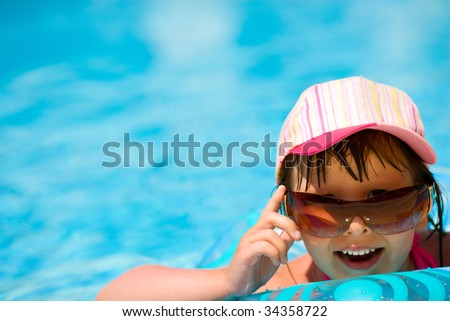 Child in pool wearing sunglasses and cap laughing - stock photo