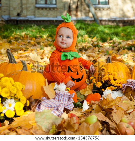 Child in pumpkin suit on background of autumn leaves - stock photo