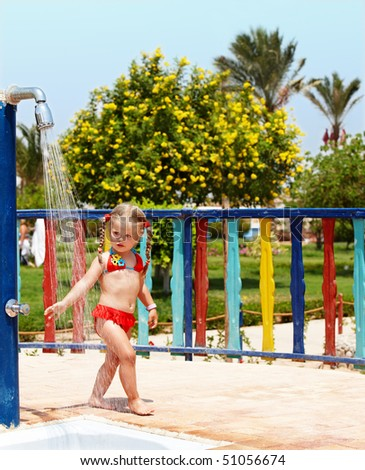 Child in red bikini take shower. Outdoor. - stock photo