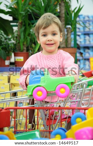 child in shoppingcart with toy car - stock photo