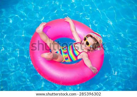 Child in swimming pool. Little girl playing in water. Vacation and traveling with kids. Children play outdoors in summer. Kid with inflatable ring toy. Swim wear and sun glasses for UV protection. - stock photo